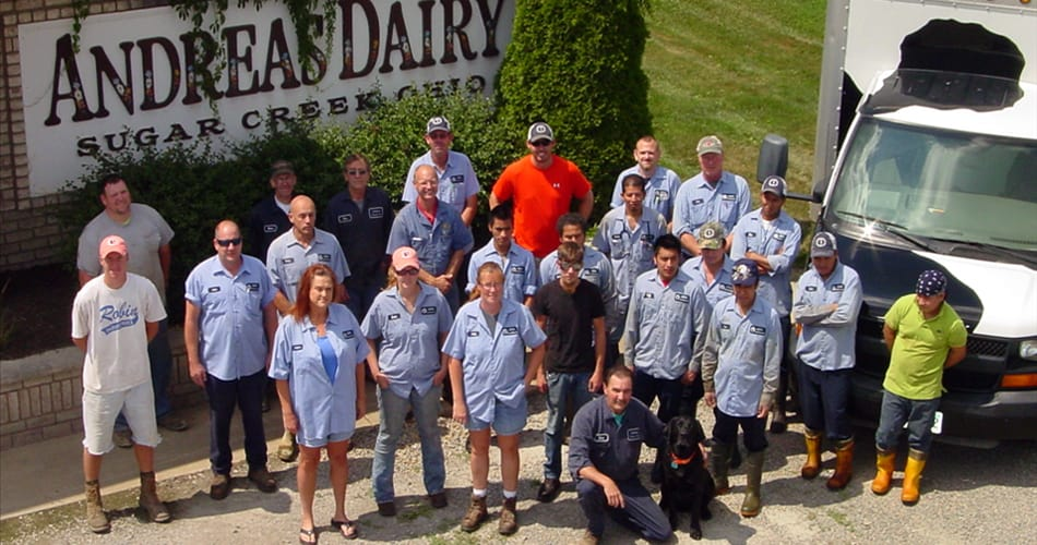 Andreas Dairy employees standing in front of the farm sign